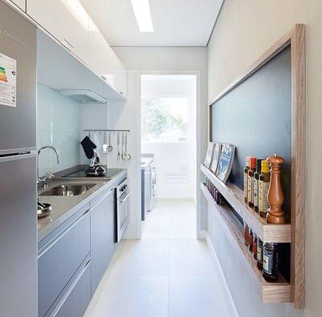Aproveitamento de espaço em cozinha linear. O quadro negro, na parede oposta aos equipamentos, têm prateleiras usadas para a guarda dos temperos mais usados.