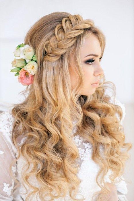 Peinados para el día de tu boda, chica usando el cabello suelto y chino con una trenza y flores como accesorios