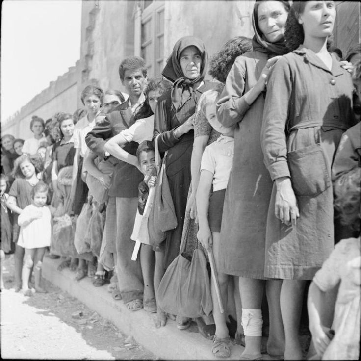 THE LIBERATION OF RHODES, 1945. Civilians on the island of Rhodes queue to get their ration books from the British military authorities. During the German occupation the local inhabitants had suffered the effects of malnutrition due to insufficient food. After the liberation of the island the British quickly began to organize food supplies, issuing people with ration books and distributing essential food stuffs. Red Cross kitchens also assisted by providing nourishing soup.