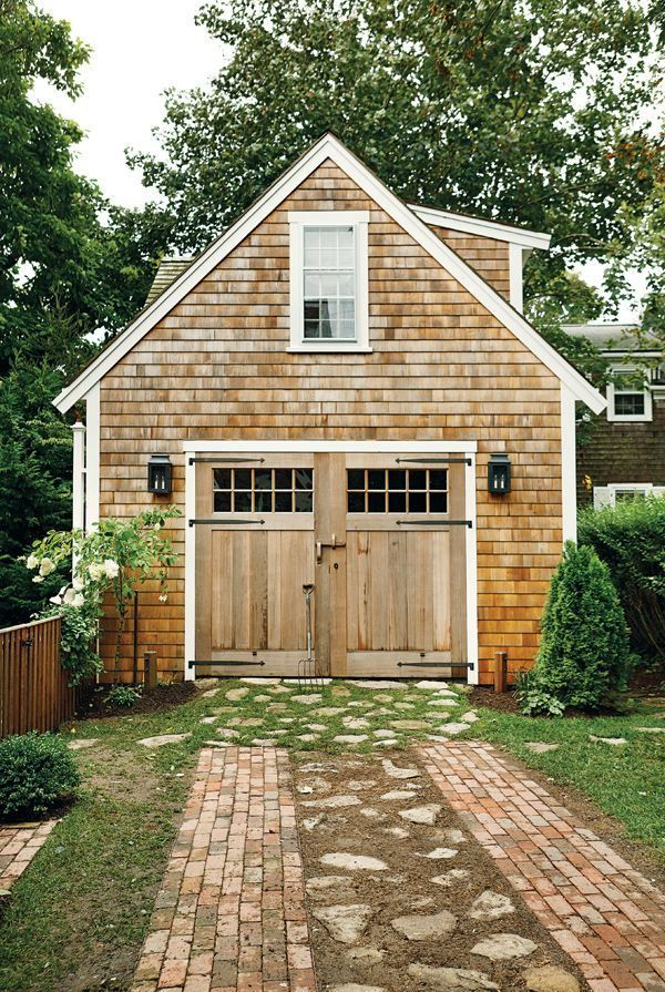 Carriage house with curb appeal - love the doors and brick and stone  driveway .