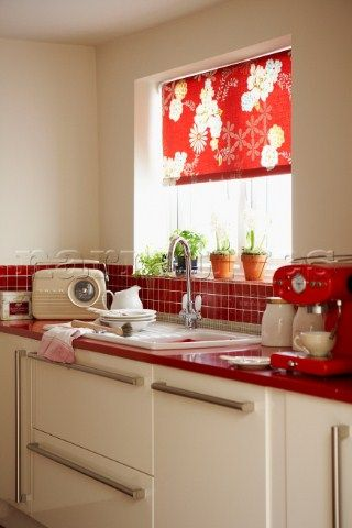 Red tiled kitchen with washing up and floral patterned roller blind