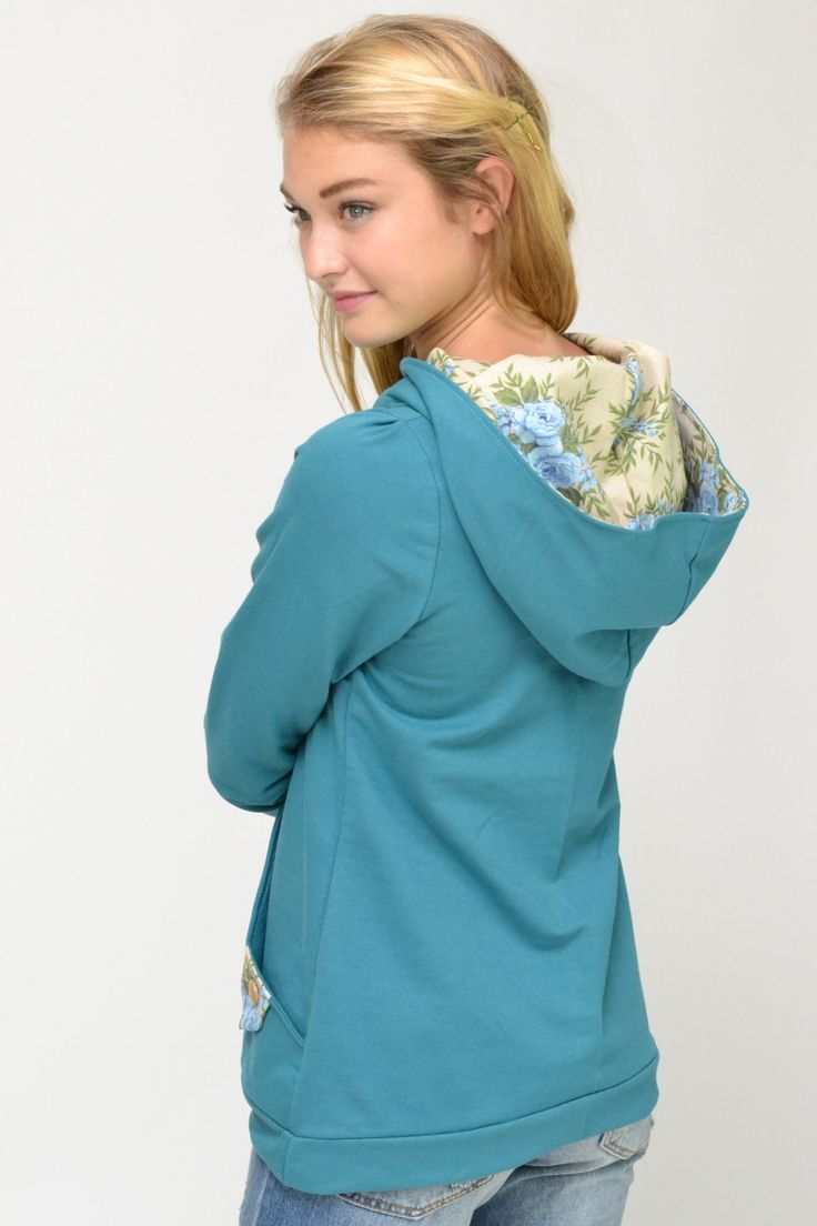 Teal hoody top with beige based blue and green floral print large side pockets and hood.
