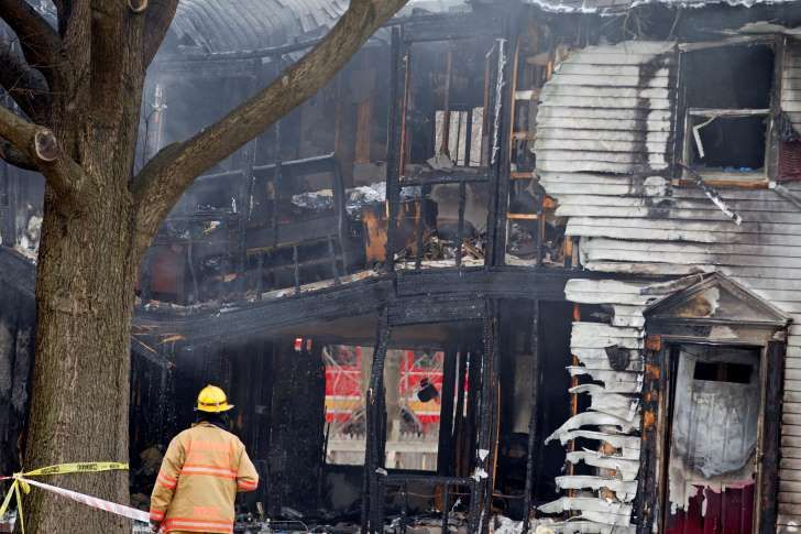 A firefighter stands outside a smoldering house where a small private jet crashed in Gaithersburg, Md., Monday, Dec. 8, 2014. A woman and her two young sons inside the home and three people on the aircraft were killed, authorities said.