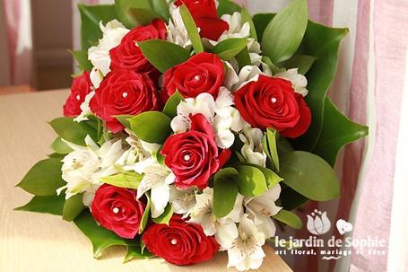 Un bouquet rond classique pour un mariage rouge et blanc !  De belles roses rouge et des alstroemeria blanc, du feuillage et un lien en cordon de laine crème !