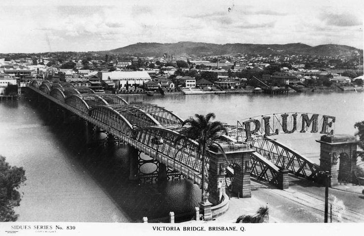 View of the Victoria Bridge and South Brisbane, ca.1940 - View of the Victoria Bridge over the Brisbane River looking across to South Brisbane. The Cremorne building and various residences are visible along the bank of the river. The 'Plume sign, advertising Plume brand petrol, appears over the entrance to the bridge on the north side.