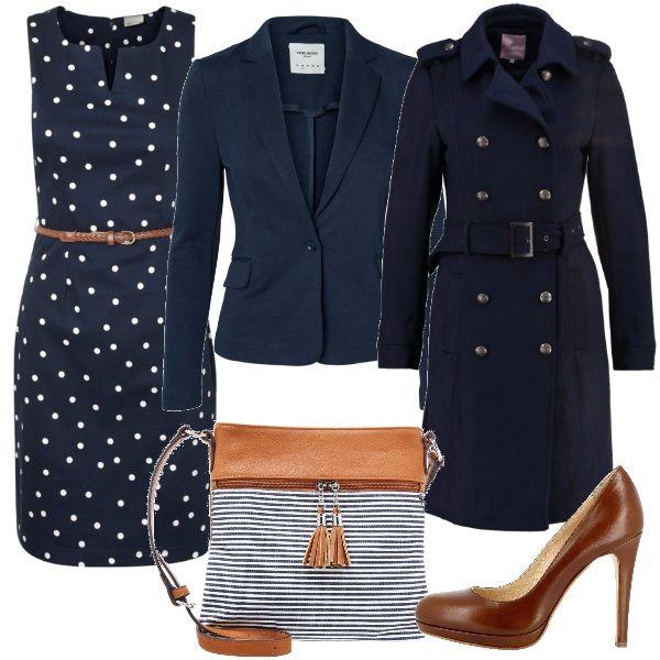 Per questo outfit: abito smanicato blu a pois bianchi con cinturina in vita, blazer blu scuro, cappotto doppio petto blu scuro con cintura in vita, décolleté color cognac, borsa a righe bianche e blu con piccole nappine.
