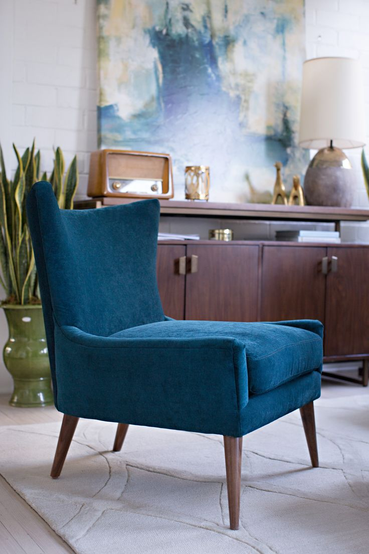 fall in love with the curvy hourglass silhouette and long tapered legs on this accent chair