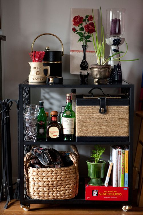 This bar cart is solid iron with black glass shelves and is one of my favorite garage sale finds EVER.  I nabbed it for $45 in Kansas City and it weighs almost 100 lbs.  I usually have a rotating selection of herbs/edible plants growing here (it's right next to the kitchen), and the onions and celery pictured didn't last long!  The picnic basket was a wedding gift and holds hostess gifts that we take with us when we visit friends, and all of the barware and trinkets on top were thrifted.