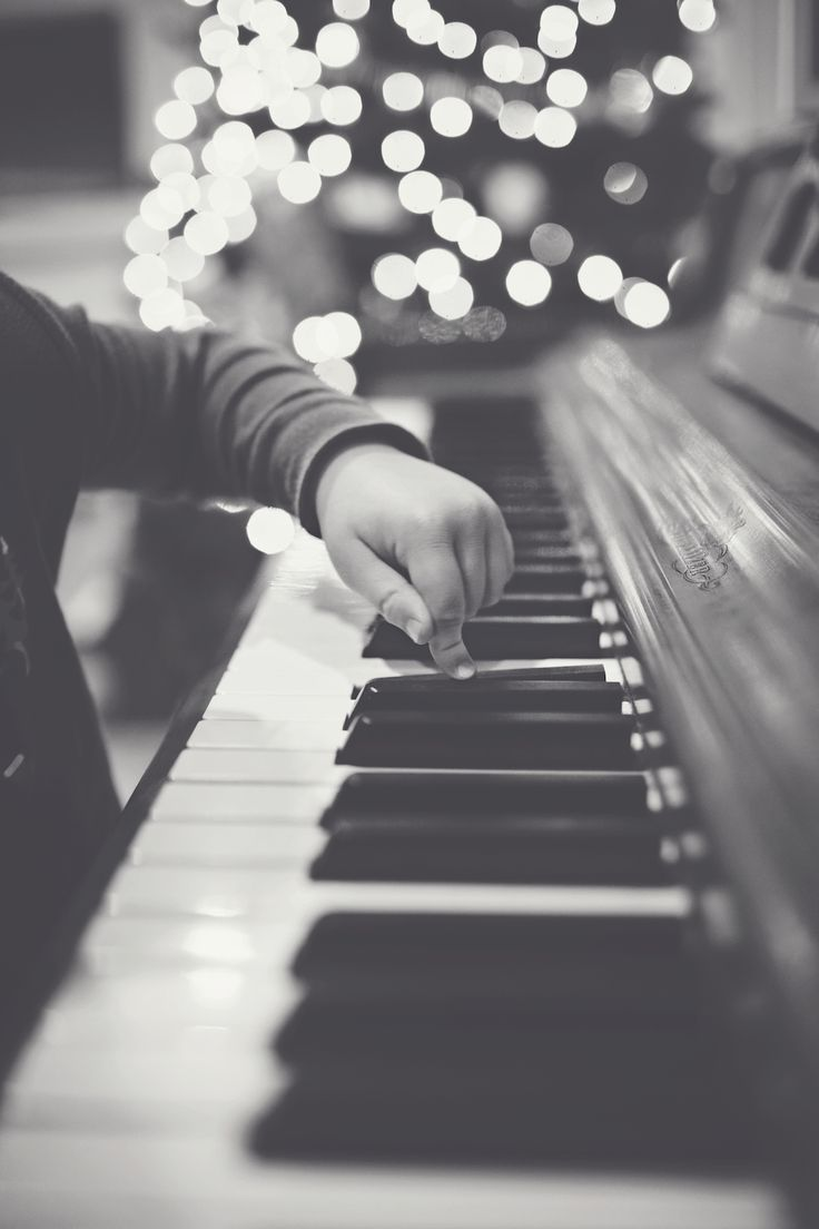 Little fingers playing the piano by the Christmas tree.