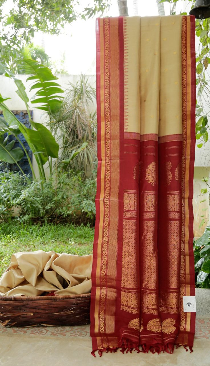 This hazelwood tan coloured gadwal silk has small gold zari bhuttas. The complementing border and pallu are in garnet red intricately woven with gold zari making it a beautiful ethnic piece
