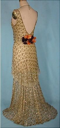 1930s bias cut evening gown.  Gold sequins and gold metallic mesh overlay.  Plunging back neckline.  At the base of the neckline is an orange and dark brown velvet rose accent, fastened at the small of the back.  The hemline length creates a slight sweep , which adds a dramatic effect.