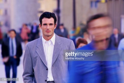 Stock Photo : Young businessman walking along crowded street (blurred motion)