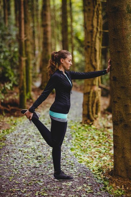 Fit brunette stretching legs against a tree in the woods