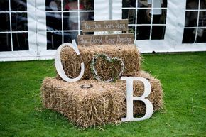 Giant C & B initial's on hay bales - Image by Nicola Norton Photography - Justin Alexander lace wedding gown & Jim Hjlem Occasions bridesmaid dresses in a rustic barn wedding with horses & stables and groom in traditional morning suit