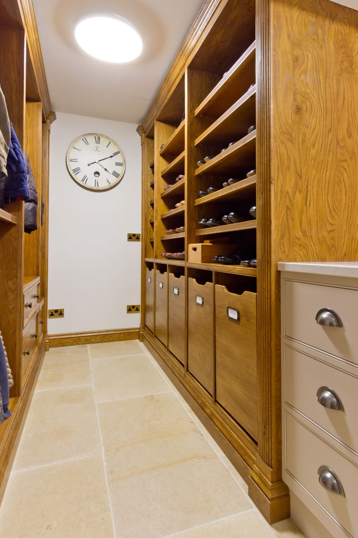 Bespoke shelving and cupboards provide a shoe room and luxury laundry storage solution in this utility room