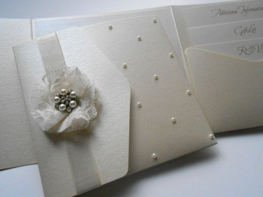 Beautiful Vintage Fleur pocket-fold wedding invitation with stunning handmade lace flower and pearl with crystal embellishment finished with a scattering of pearls! x