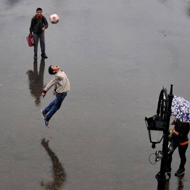 Un bambino gioca a calcio in una strada bagnata: in questo periodo in India è la stagione dei monsoni
