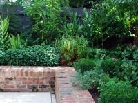 Raised red brick retaining wall, garden bed border