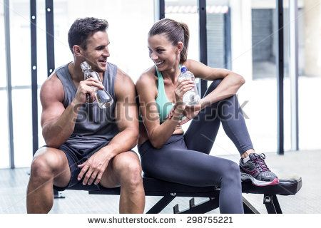 Muscular couple discussing on the bench and holding water bottle - stock photo