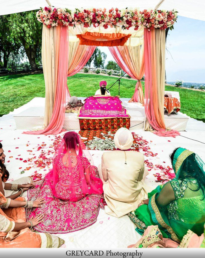 Sikh Wedding at Pacific Palms Resort. The venue put a subflooring down on top of the grass. The Guru Granth Sahib was raised to ensure it was higher than the seated guests. Rumaals were provided to the guests and show racks were setup as well.  Photography: Greycard Photography www.shaadishop.co