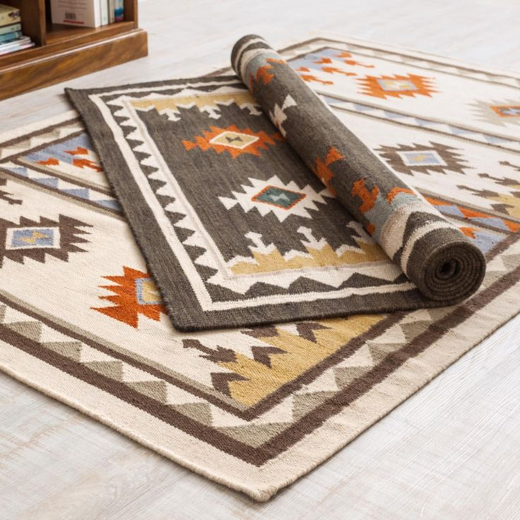Orrin Kilim Rug filled with Apache motifs that are hand-loomed in India using flat weave traditional techniques. Choose from a Natural or Charcoal base colour.