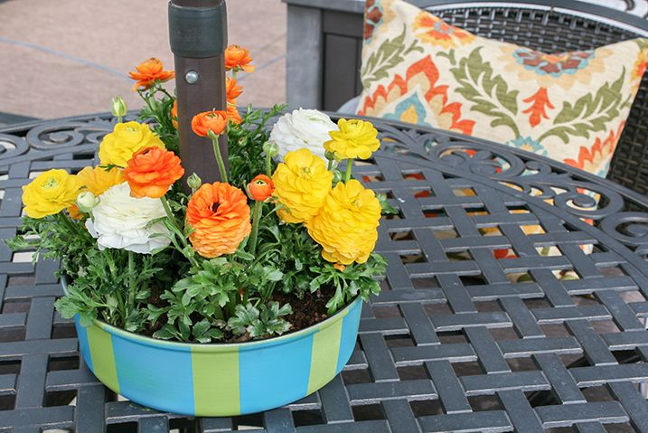 Flower planter painted green and blue sitting in the center of a patio table with the umbrella rod going through the middle