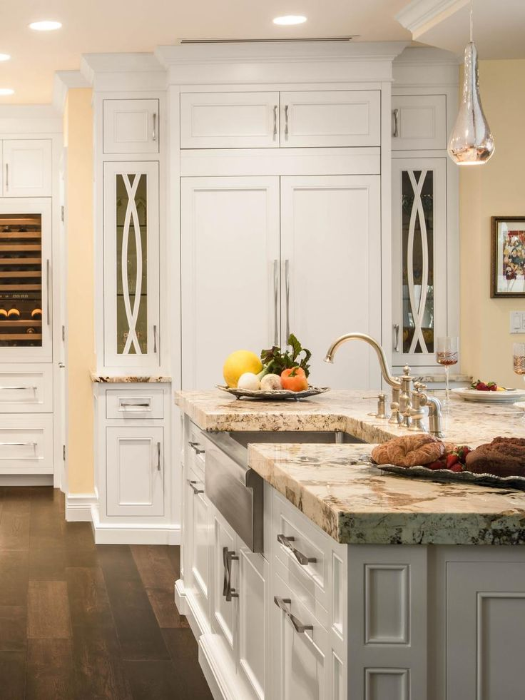 Custom+cabinets+line+this+chef's+kitchen+while+a+large+center+island+topped+with+granite+is+equipped+with+a+modern+version+of+a+farmhouse+sink.+