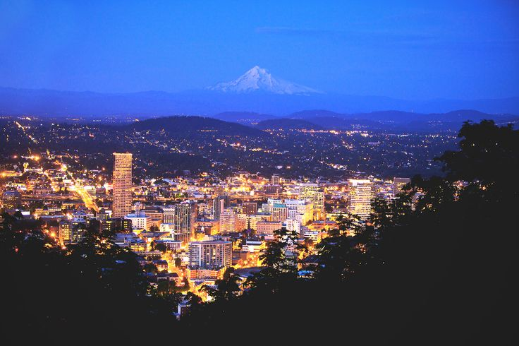 A lighted up Portland city with a snow capped Mt Hood dimly visible in the distant night sky