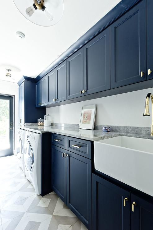 Stunning contemporary laundry room is fitted with blue shaker cabinets accented with rectangular brass knobs and fixed to a white wall above an enclosed white front loading washer and dryer.