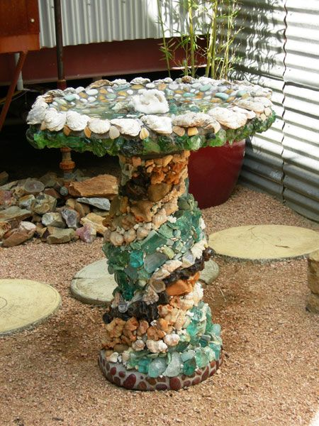 This birdbath was created with slag glass, oyster shells, geodes, river rocks, various types of quartz and minerals and is accented with pearls. There is no surface left untouched. The bottom of the bath is tiled with green recycled glass. The spiral motion of the slag glass, shells and minerals flows up to the top where the quartz, river rock and pearls sparkle and shine in the sunlight and water.