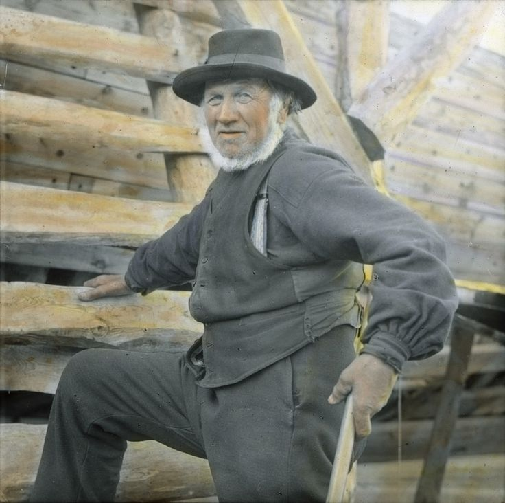 Rosendal Skibsbygger, Norway. Håndkolorert dias. En mann med hatt og vest står med ene foten og hånda på en trestige, i den andre hånda holder han et redskap, antakelig en øks.