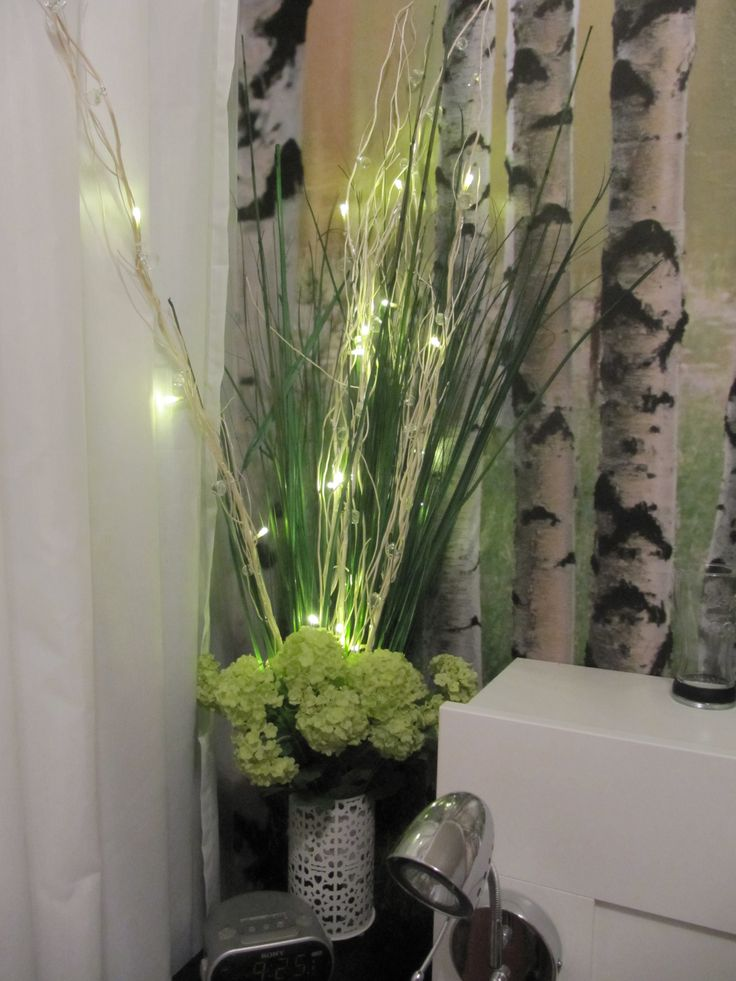 flowers and branches with lights in a vase. Bedroom decoration