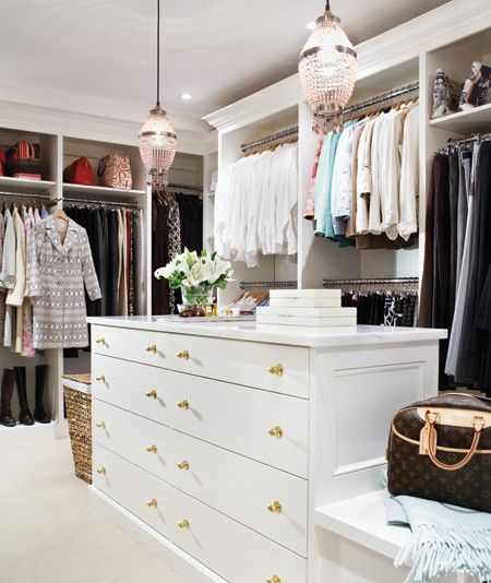 A marble-topped island and a pair of crystal chandeliers are two of the many fabulous features of this large, high-end closet.
