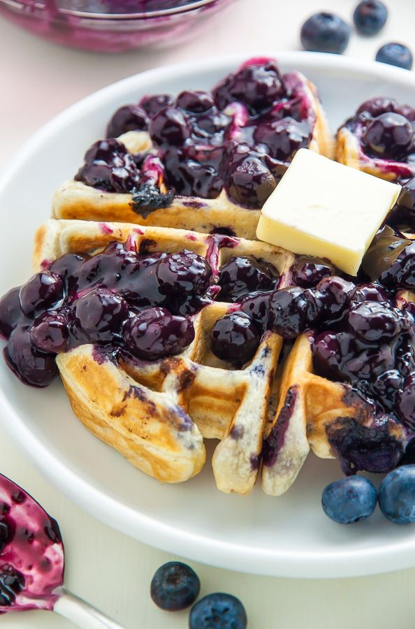 Homemade Greek Yogurt Blueberry Waffles topped with fresh blueberry sauce.