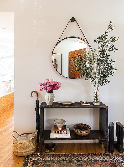 """The entry illustrates the couple's ethos of """"less is more."""" A console from Galerie Half holds pottery from Californian and Japanese ceramists. (David Korty and Akio Nukagaare favorites.) The front door, designed by Jed, is seen in the BDDW mirror's reflection."""