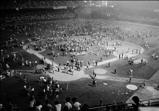 Fans stream onto the field after Disco records are destroyed as part of the Disco Demolition Night July 12, 1979 at Comiskey Park in Chicago, IL
