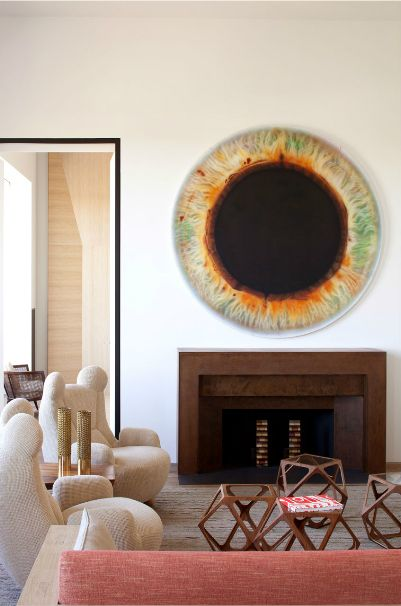 The tables, those chairs, clean mantle and that eye art!!! Interior by Pierre Yovanovitch.