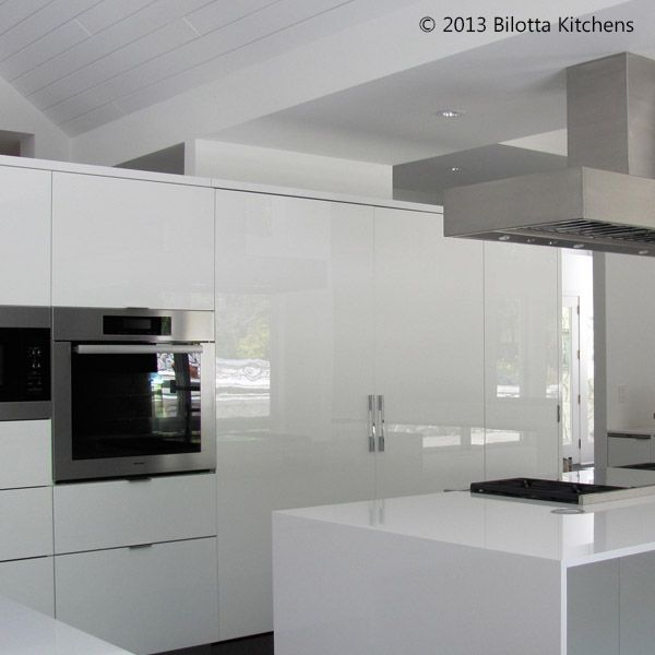 This kitchen designed by Daniel Popescu of Bilotta Kitchens features high-gloss white cabinetry with a black porcelain tile floor.