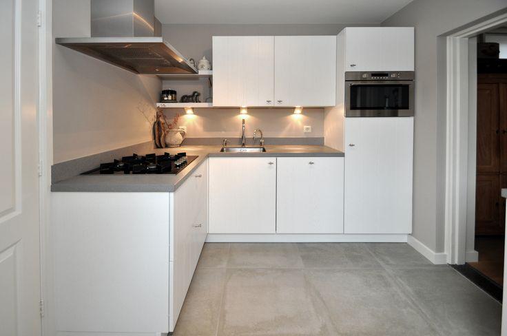 Leuke compacte witte keuken opgeleverd met wit gelakte houten fronten. Betonlook vloertegels en een composiet werkblad met RVS onderbouw spoelbak.
