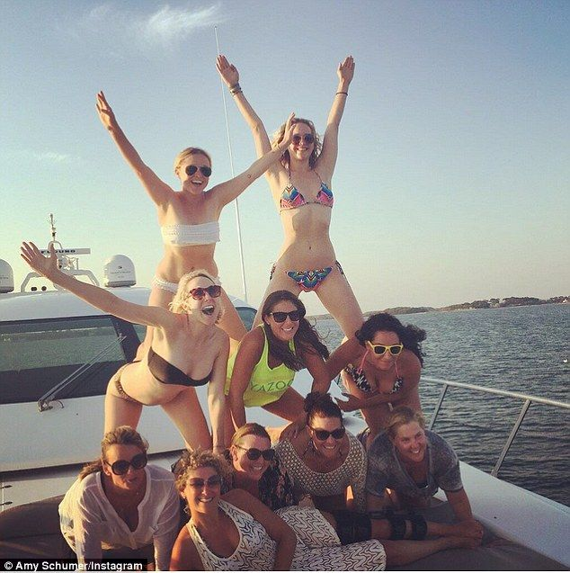 At the top! Amy Schumer shared a photo of J-Law in a colourful two-piece bikini (top right) as she stood atop of a human pyramid - with the comedienne (bottom right) providing structural support on Thursday