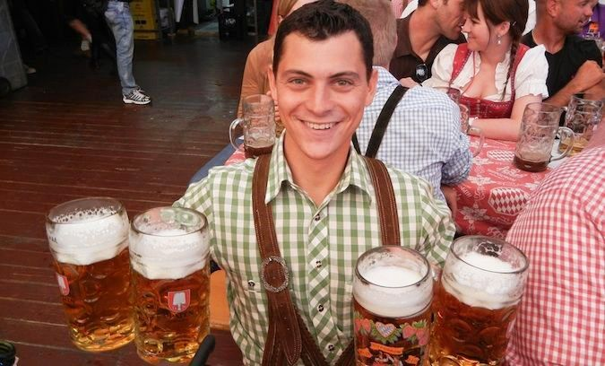 Nomadic Matt celebrating Oktoberfest in Germany with many beers