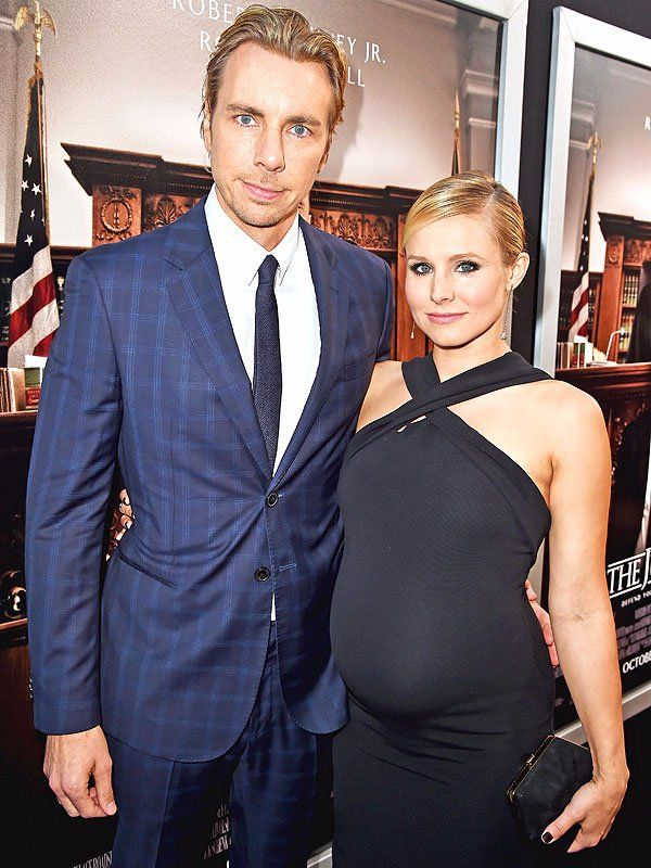 A pregnant Kristen Bell standing next to husband Dax Shepard