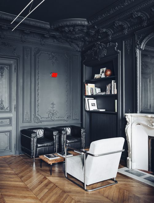 Black moldings and woodwork with black and white leather chairs, an oversized wall mirror and parquet hardwood floors.