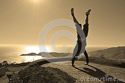Happy young man makes handstand in front of the Pacific ocean in San Francisco. Image taken on a sunny day as a twilight shoot. He expressed his happy feeling about the vacation  trip.