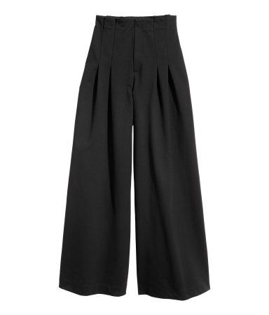 Black. Pants in thick jersey. Narrow cut at top with a high waist, pleats, and zip fly with hook-and-eye fastener. Wide, super-flared legs.