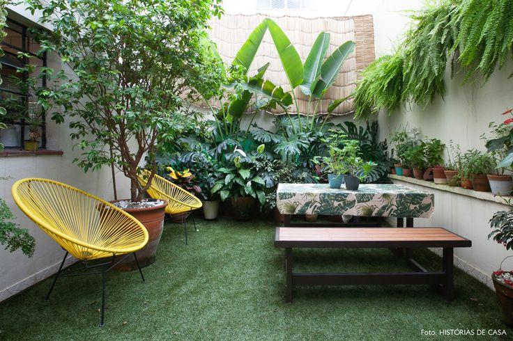 Apartamento no centro de São Paulo com jardim. Destaque para folhagem tropical, poltronas Acapulco e mesa de madeira.