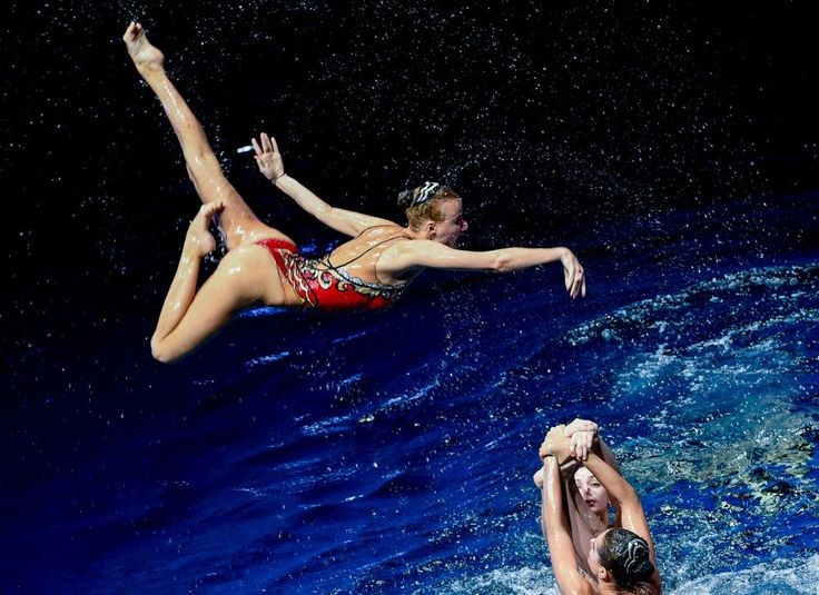"""Members of the Russian synchronized swimming team perform in the theater-and-circus show on water """"Secret of the Subterranean Sea"""" in Moscow."""