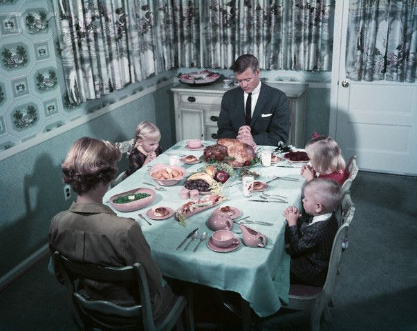 Father says grace before an iconic looking 1950s family tucks into their lovely Thanksgiving dinner.