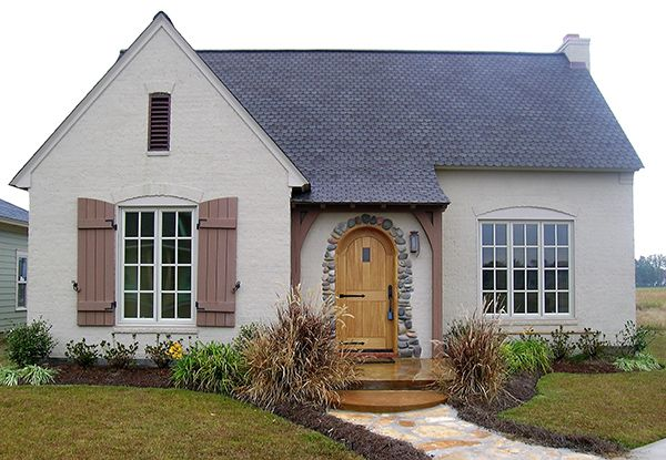 Beautiful stone frames the arched entry into this charming cottage. Tall 12'…