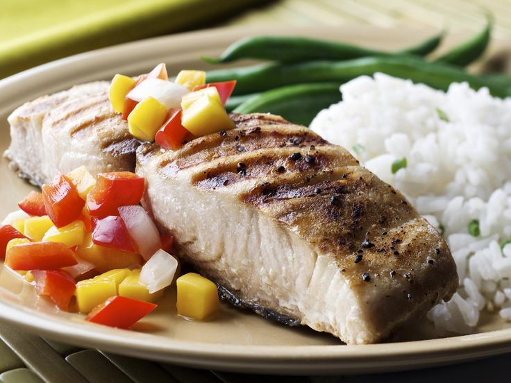 """SEVERAL MORE IN THIS SERIES. Grilled cutlet (open steak cut) of mahi-mahi (dolphin fish) with a fresh mango, pepper and onion salsa; rice and green beans on the side."""